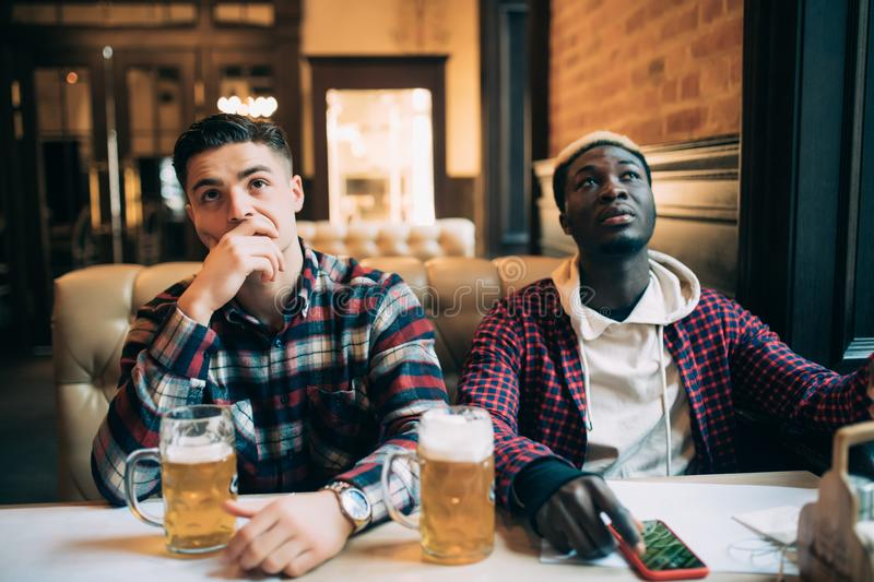 Upset male friends watching sport game or football match and drinking beer at bar or pub stock image
