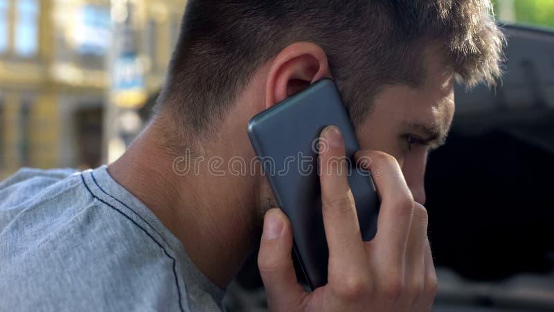 Upset male speaking on smartphone, standing near his broken car, breakage stock images