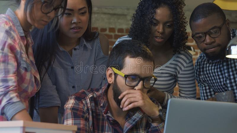 Upset man announcing of bad news to colleagues stock photo
