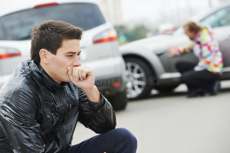 Upset man after car accident. Adult upset driver man in front of automobile crash car collision accident in city stock images