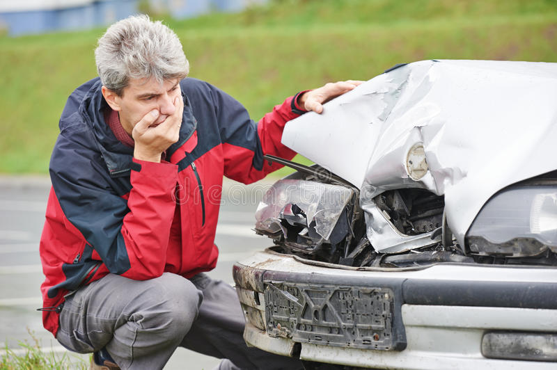 Upset man after car crash. Adult upset driver man in front of automobile crash car collision accident in city