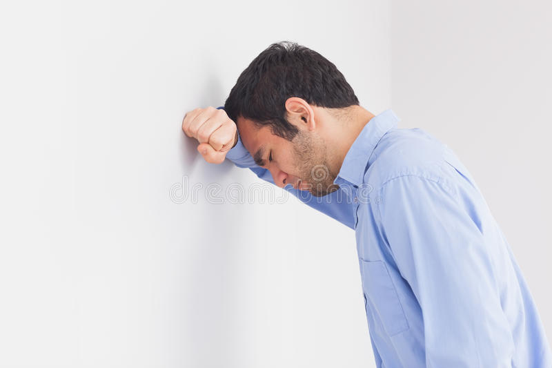 Upset man leaning his head against a wall stock images