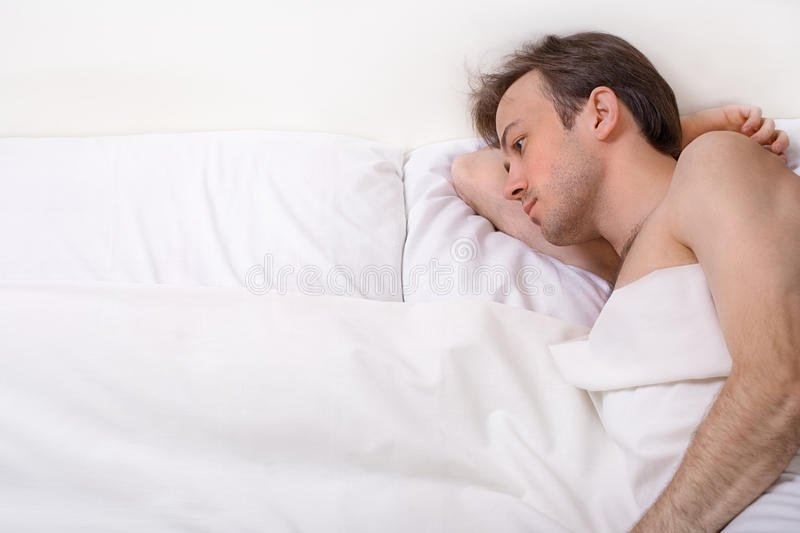 Upset man lies in the bed royalty free stock photo