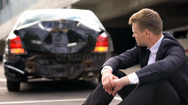 Upset man sitting on road after car crash waiting police, lack of experience royalty free stock photo