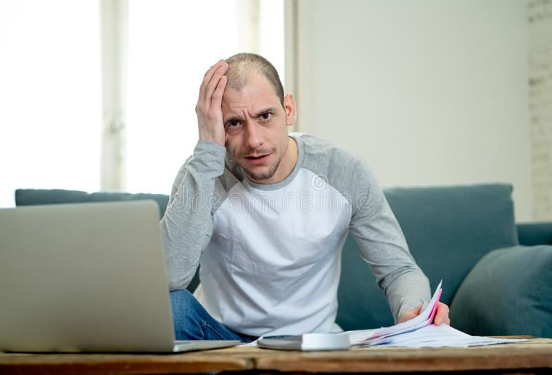Upset man in stress paying credit card online debts and counting finance with laptop and bank papers. Desperate entrepreneur young man managing finances royalty free stock photo