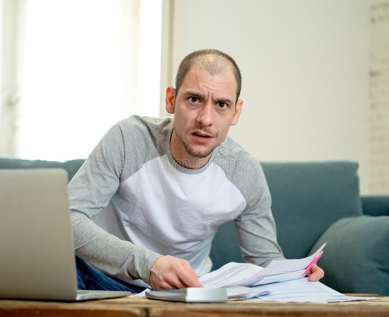 Upset man in stress paying credit card online debts and counting finance with laptop and bank papers. Desperate entrepreneur young man managing finances stock images