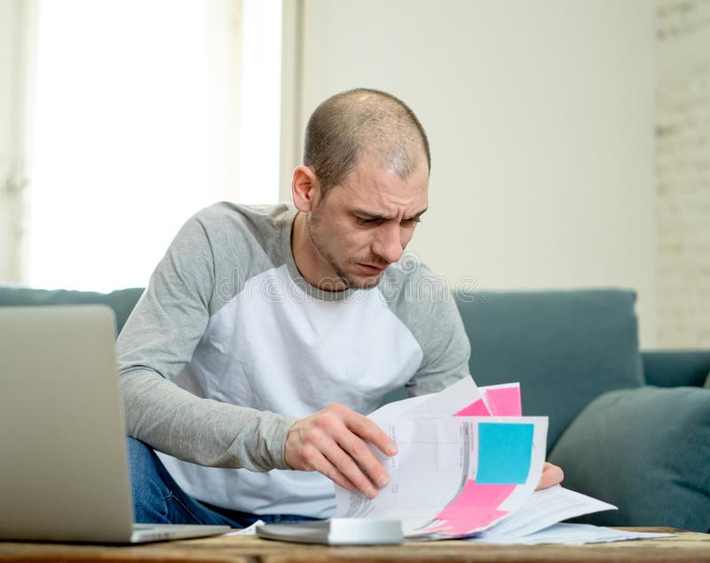 Upset man in stress paying credit card online debts and counting finance with laptop and bank papers. Desperate entrepreneur young man managing finances royalty free stock images