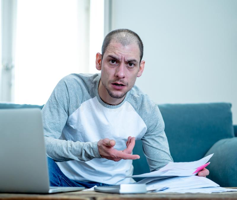 Upset man in stress paying credit card online debts and counting finance with laptop and bank papers. Desperate entrepreneur young man managing finances stock photography