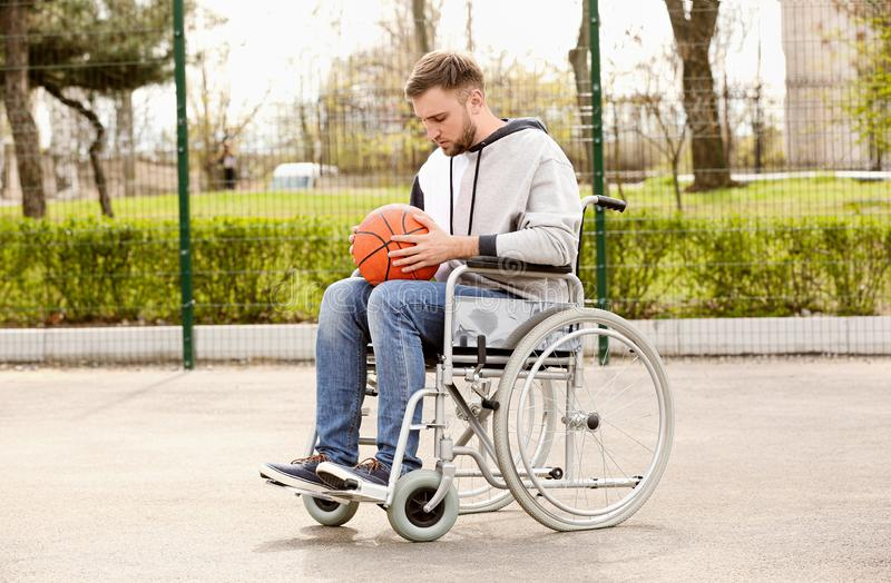 Upset man in wheelchair with ball on ground stock photography