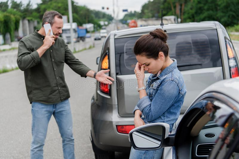 Upset man and woman near cars after. Car accident royalty free stock image