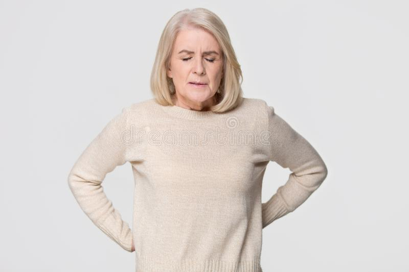 Upset old woman touching back feeling pain isolated on background royalty free stock photos