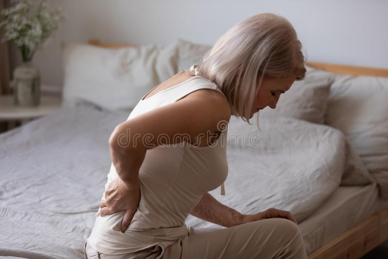Upset mature woman suffering from backache, rubbing stiff muscles stock image