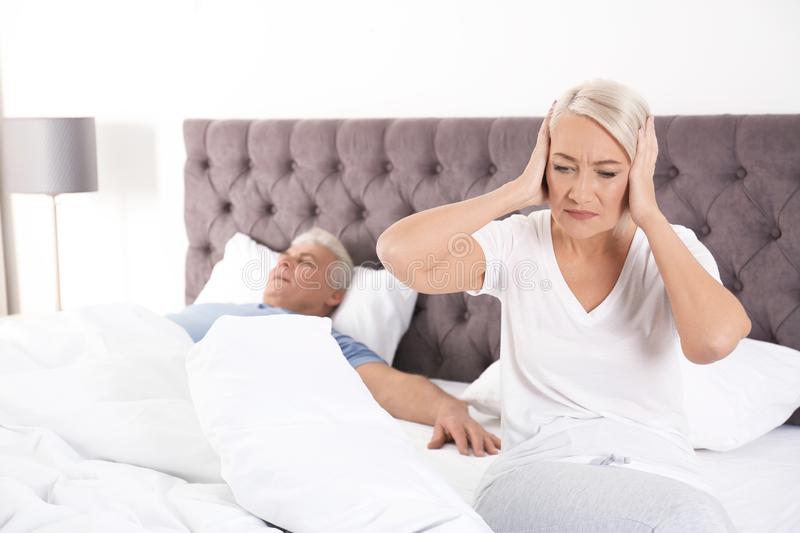 Upset mature woman sitting on bed near her sleeping husband at home. royalty free stock photography