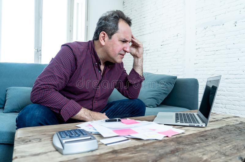 Upset middle aged man stressed about credit card debts and payments not happy accounting finances. Mature attractive man on computer looking stressed and worried stock photo