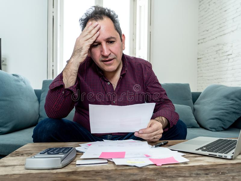 Upset middle aged man stressed about credit card debts and payments not happy accounting finances. Mature attractive man on computer looking stressed and worried stock images