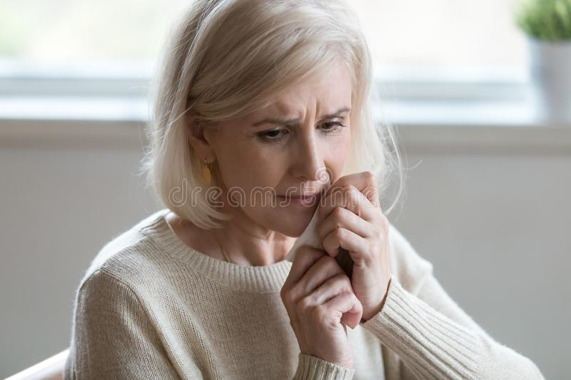 Upset middle aged woman wiping tears crying feeling depressed lo stock photo