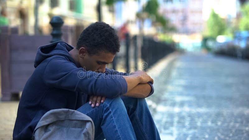 Upset multi-ethnic boy lonely sitting on sidewalk, family conflict, rebellion. Stock photo stock photography