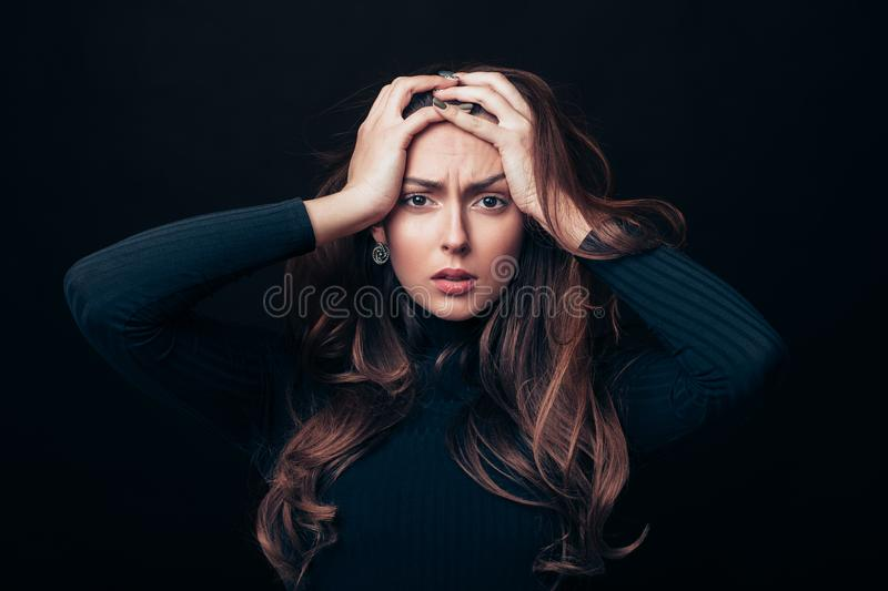 Upset offended beautiful woman holding her hands on head isolated on black background royalty free stock photo