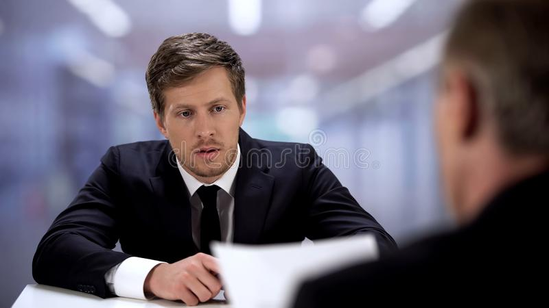 Upset office worker listening boss, mistakes made in annual report, bad result. Stock photo stock image