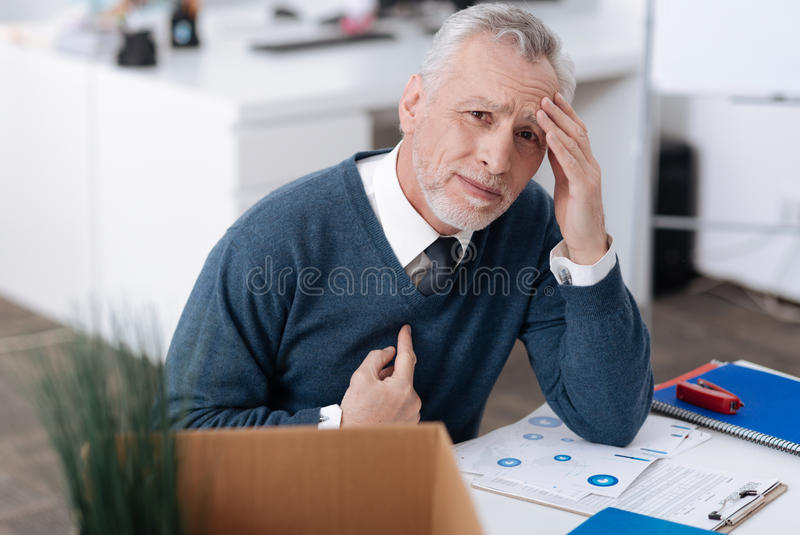Upset office worker wrinkling his forehead. They fired me. Crying man wearing blue cardigan pointing himself while putting left hand on the forehead stock photography