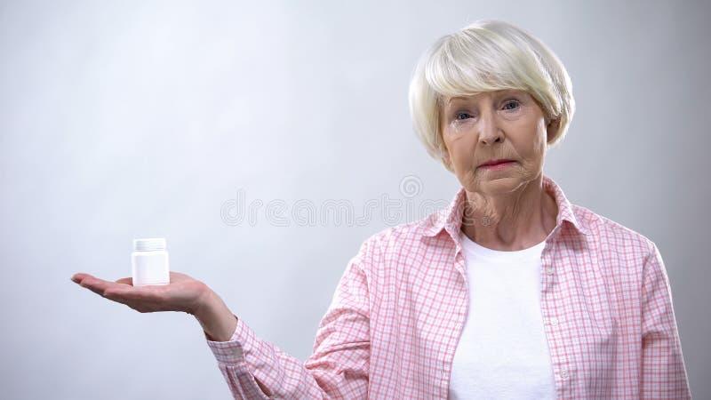 Upset old lady holding pills bottle, ineffective treatment, bad quality medicine. Stock photo royalty free stock photo