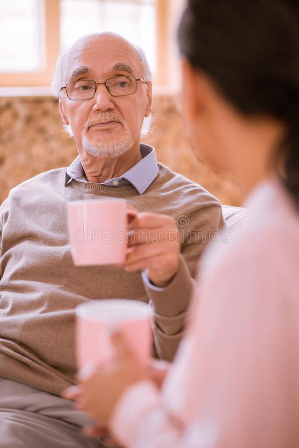 Upset old man being deep in his thoughts. That is a pity. Serious male person looking at brunette women while having sincere conversation stock photography