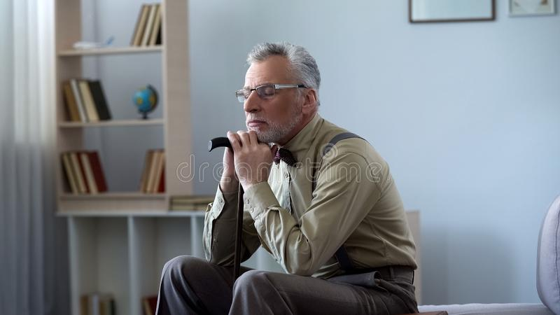 Upset old man leaning on walking stick, taking nap at midday, feeling lonely stock photos