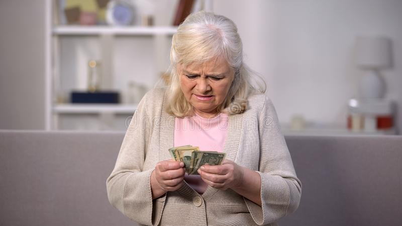 Upset old woman counting dollars, low living standard, pension age increase royalty free stock photo