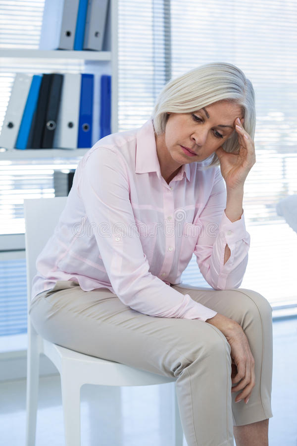 Upset patient sitting at medical clinic stock photo