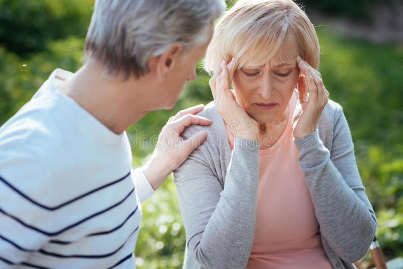 Upset pensioner feeling terrible pain in the head outdoors. Crying from my helplessness. Confused disappointed old women touching her head and feeling pain while stock photos