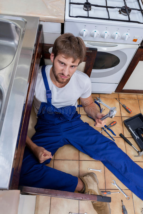 Upset plumber trying to fix the sink. Upset plumber in blue uniform trying to fix the sink royalty free stock images