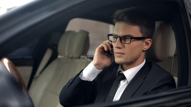 Upset politician talking on phone, sitting in car, business trip, travelling stock image