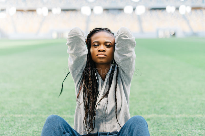 Upset portrait of the beautiful afro-american teenager touching the head at the background of the stadium. stock images
