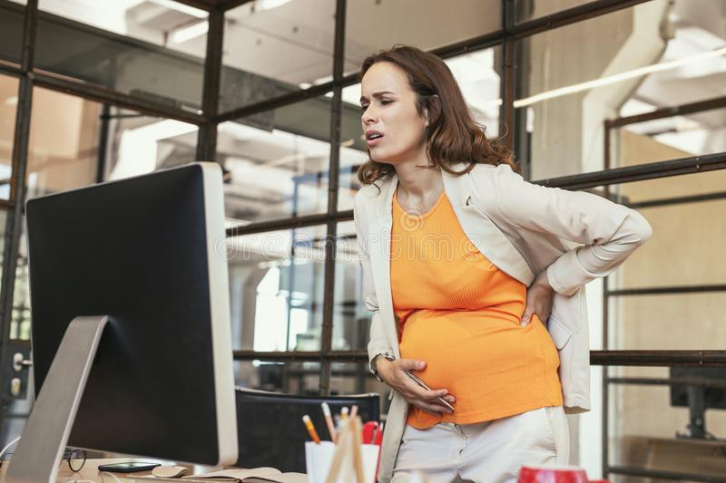 Upset pregnant CEO suffering from indigestion. Discomfort during pregnancy. Low angle of ill pregnant CEO standing and supporting belly royalty free stock image
