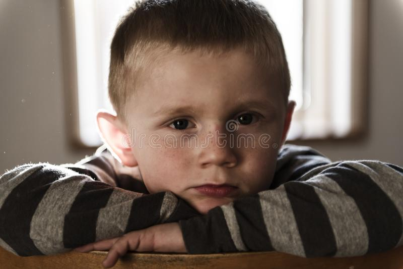 Upset problem child sit on chair concept for bullying, depression stress. A Upset problem child sit on chair concept for bullying, depression stress stock image