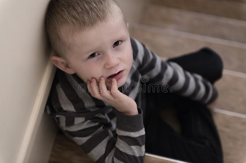 Upset problem child on the staircase concept for bullying, depression stress. Or frustration stock images