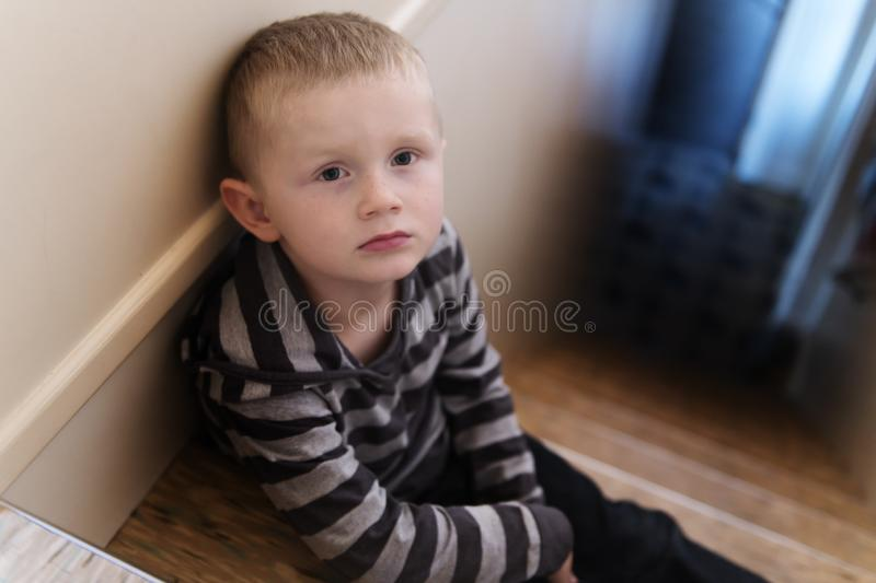 Upset problem child on the staircase concept for bullying, depression stress. Or frustration stock photo