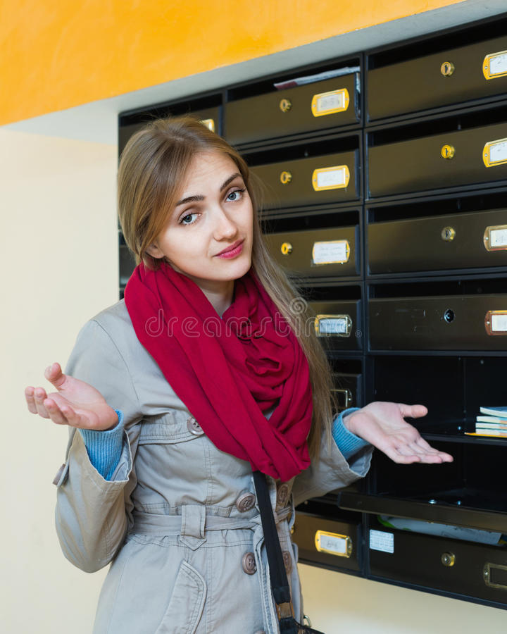 Upset sad adult girl standing near empty mail box. In hall stock images