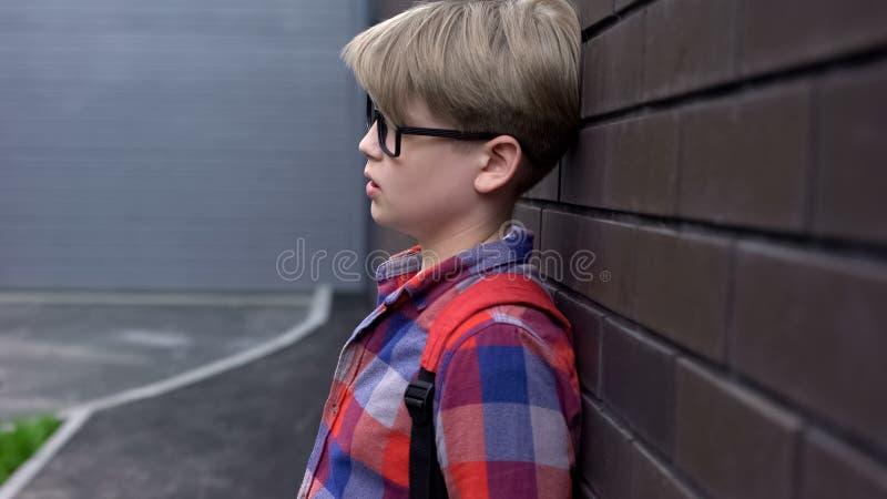 Upset schoolboy standing near wall, statistics of bullied children, awareness. Stock photo stock images