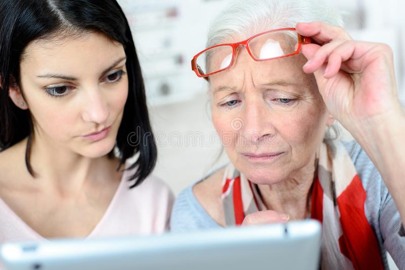 Upset senior lady watching tablet with granddaughter stock photos