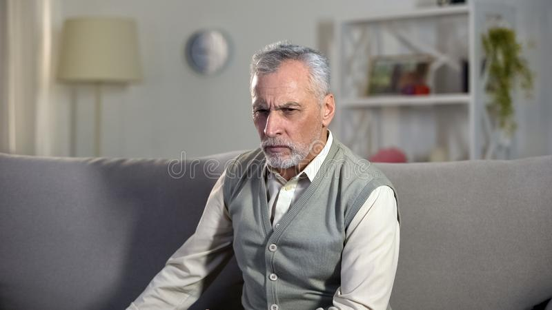Upset senior male sitting alone in hospice, thinking about life problems, aging royalty free stock photos