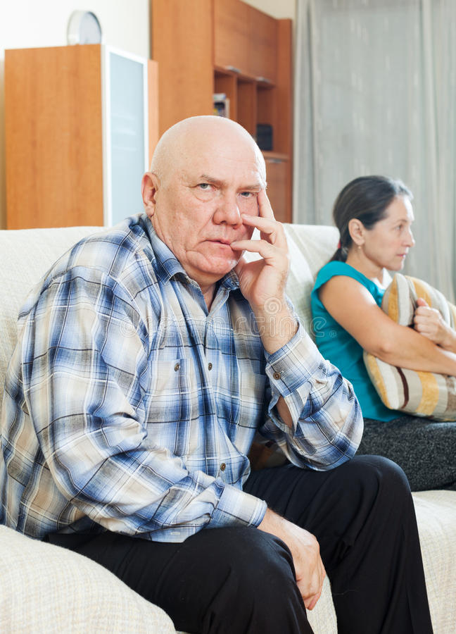 Upset senior man against sad wife. Family quarrel. Upset senior men against sad wife at home royalty free stock image