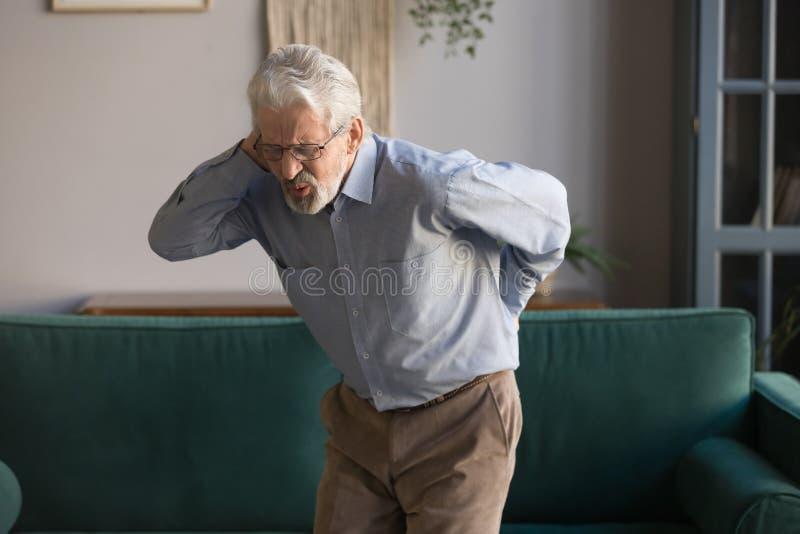 Upset senior man feeling back pain injury standing at home stock image