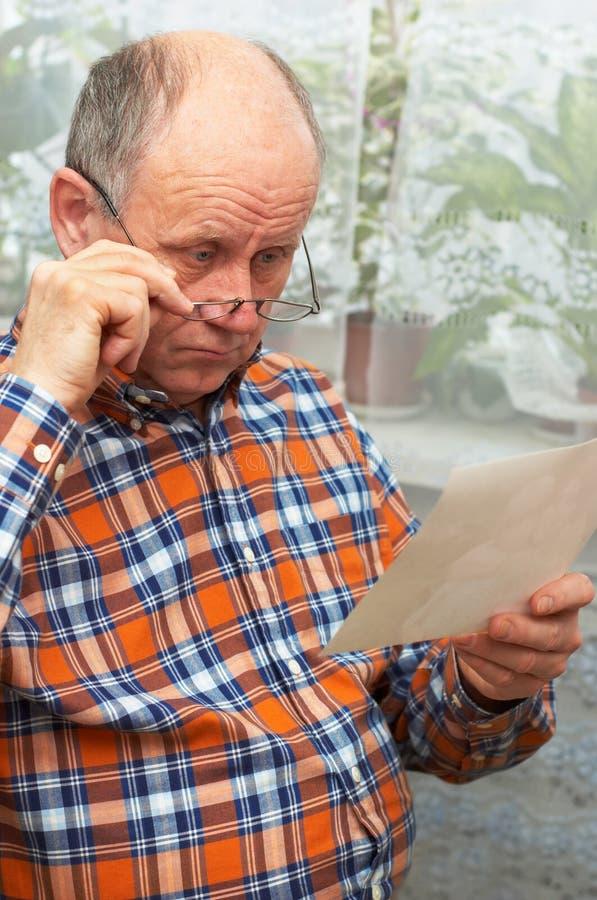 Upset senior man looks at photo stock photos