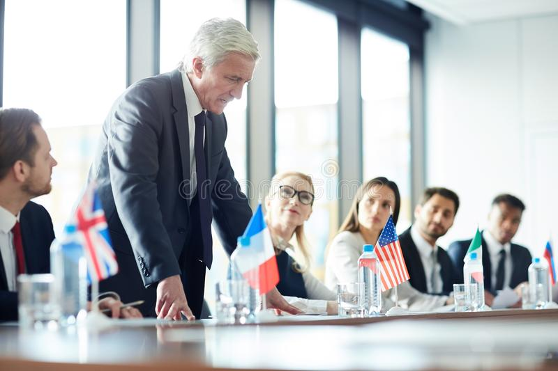 Upset senior politician talking at meeting. Upset displeased senior politician in suit standing up and talking about his position loudly at meeting, government stock photography