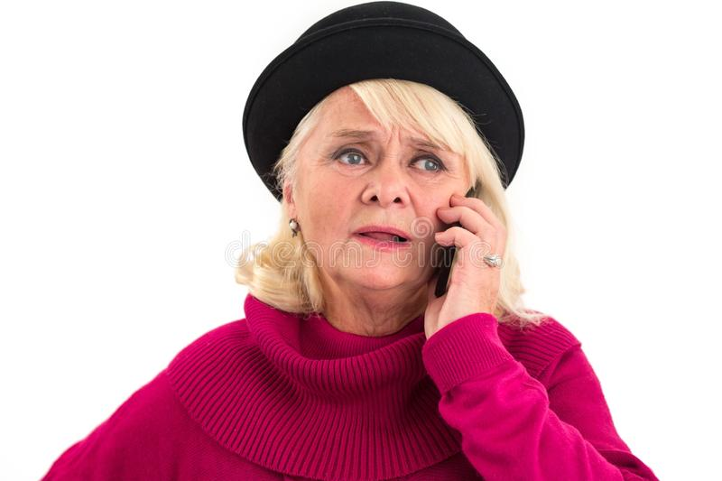 Upset senior woman with cellphone. Old woman on white background. Sad news from home stock images