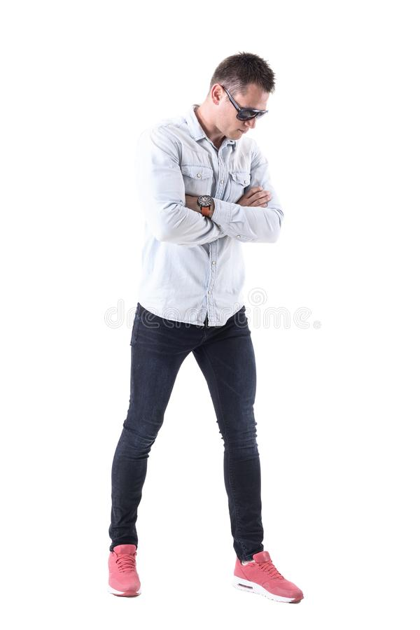 Upset serious handsome adult man with sunglasses with crossed arms looking down stock photography