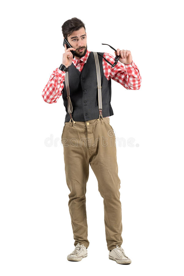 Upset serious hipster explaining on the phone holding sunglasses stock image