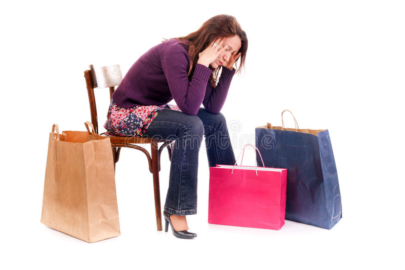 Upset shopping. Woman seated on chair very tired and stressed after shopping royalty free stock images