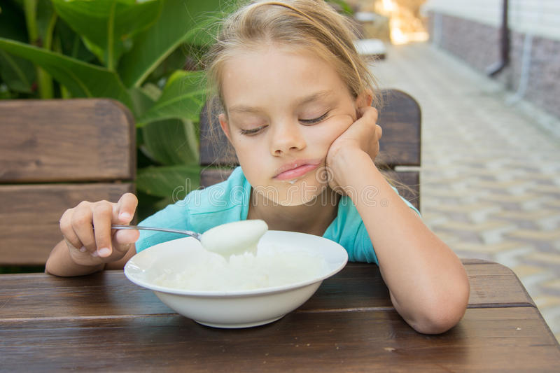 Upset six year old girl looking sadly at the semolina in a spoon at breakfast stock photography